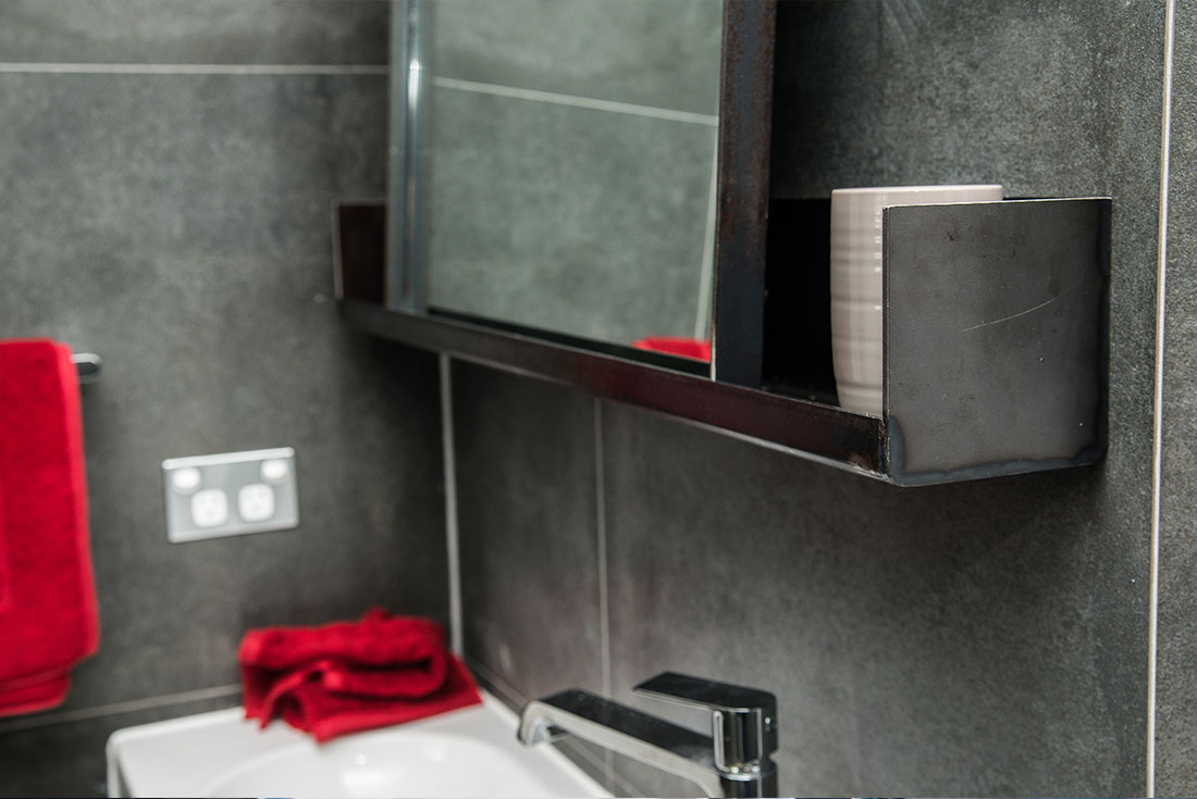 Custom black steel bathroom furniture- bathroom vanity and mirror ledge by WETT Solutions, Sydney.